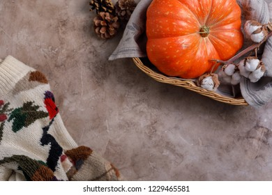 Fall and winter fashion still life in minimalist style. Cozy wool warm sweater,pumpkin, jewelry. Copy space, blogging concept.