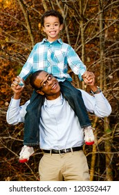 Fall or winter portrait of African-American father and son outdoors at park