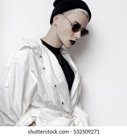 Fall Winter Trend hipster model. Swag.Girl Minimal style. Beanie cap and stylish sunglasses. Vintage Glamour. Trendy white coat. Outfit Black fashion stylish Makeup lips focus on white