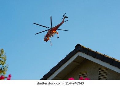 Fallbrook, California, USA – July 29 2018: CalFire helicopter circles  wildfire as it readies to drop water on fire near Fallbrook, California in San Diego County.
