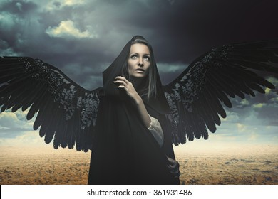 Fallen angel in a desert and stormy landscape. Fantasy and surreal
