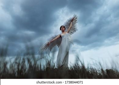 Fallen angel on earth.  Girl in the wings dancing in the sky