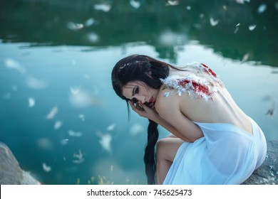 Fallen Angel. A young girl with torn off wings, desperately wanders on the ground with hope in her eyes. Art Photography. Long dark hair. Background watercolor river.