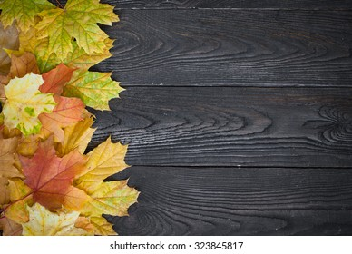 Fallen autumn leaves on a dark wooden table. Top view, copy space.