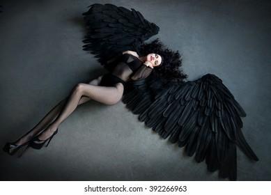 Fallen black angel with wings. Sexual woman