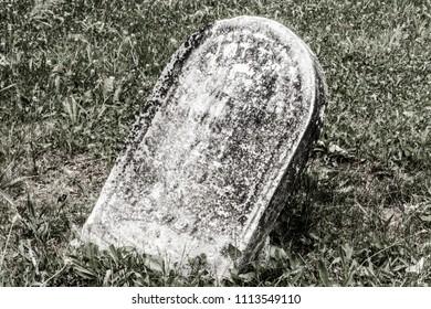 Fallen creepy headstone in a cemetery IV