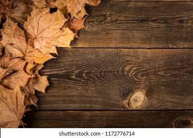 fallen dry leaves on wooden plank background