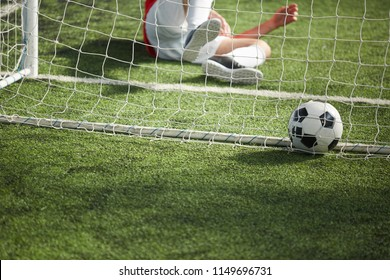 Fallen goalkeeper lying on green football field and soccer ball in gate