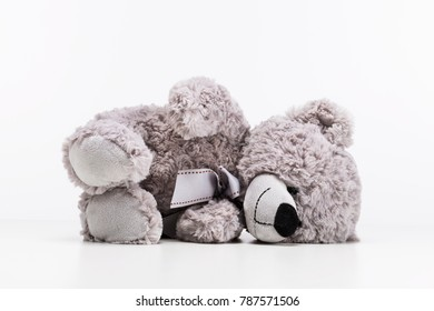 Fallen gray fur plush toy on white background. Teddy bear felling sick and lonely laying down