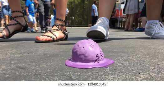 Fallen ice cream ball melting on hot ground.