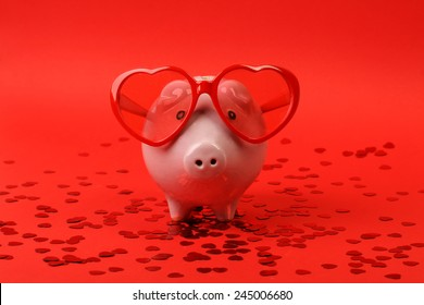 Fallen in love piggy bank with red heart sunglasses standing on red background with red shining heart glitters