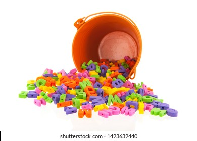 Fallen orange bucket with many foam letters isolated over white background