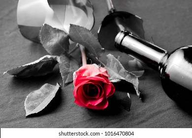 Fallen rose with a broken wine glass. Rose is red and background is black and white.