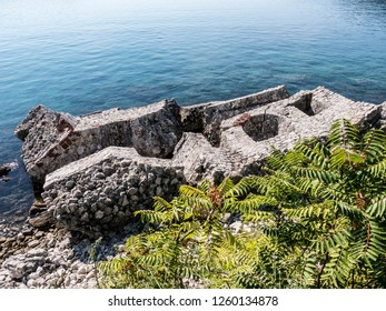 Fallen ruined old stone block citadel wall with loopholes in sea water top view