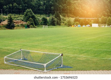 Fallen soccer football gate lying on empty green field with camping tents in the background