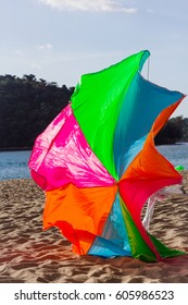 The fallen sun umbrella. The bright sun umbrella lying on a shore filled with the wind. Vertical outdoors shot.