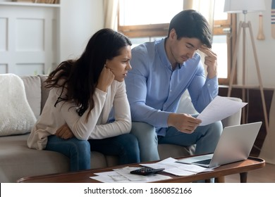 Falling behind with rent. Concerned worried young married couple sitting on sofa at home office studying paper letters from bank informing about debt bankruptcy. Financial loss unprofitable investment