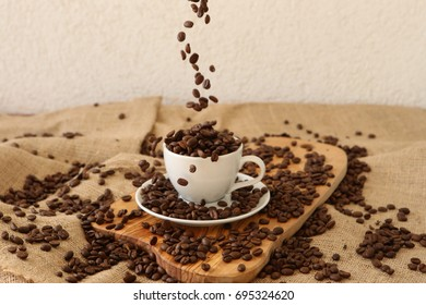 Falling coffee beans into the porcelain cup