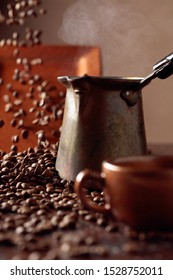 Falling coffee beans and old copper coffee maker. Copy space. Selective focus.