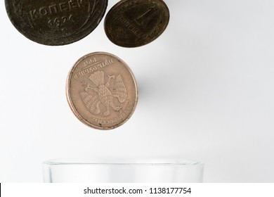 falling coins in glass form, white background metal coins