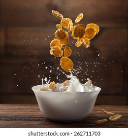 Falling corn flakes with milk splash on wooden background