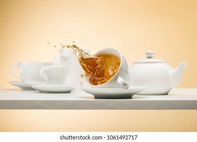 falling cup of tea on white table with tea splashing