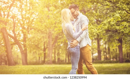 Falling deeper in love every moment they're together. Young smiling couple in hug standing at park.