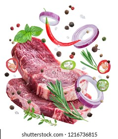 Falling down meat steaks and spices. Flying motion effect of cooking process. File clipping path.