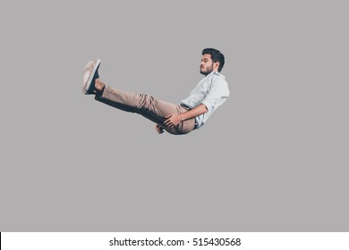 Falling down. Mid-air shot of handsome young man falling against grey background