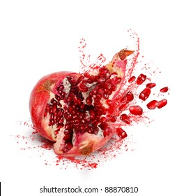 Falling down ripe pomegranate with cracks and splashes of juice and seeds on white background