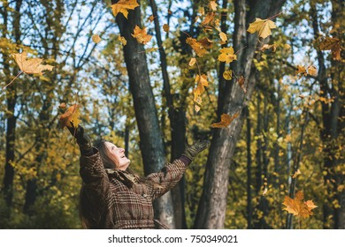 Falling and flying autumn leaves and woman in the forest