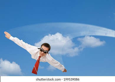 Falling or flying businessman with dark goggles and white contrail - against blue sky