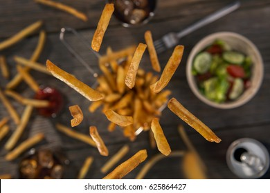Falling french fries on a old wooden table