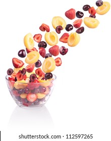 Falling fruit in a glass bowl. Isolated on white.