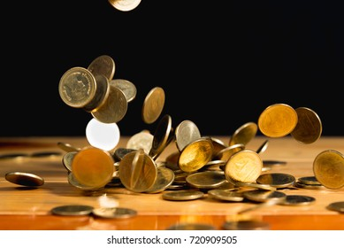 Falling gold coins money on wooden table with black wall, copy space, business wealth concept. thin focus