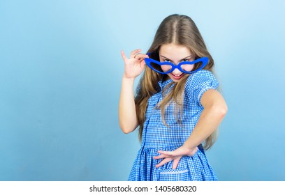 Falling in love with my goggles. Adorable little girl wearing fancy goggles. Cute smal child with fashion goggles accessory. Choosing trendy goggles perfect for her glamorous lifestyle, copy space.