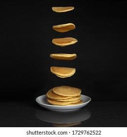 Falling pancakes into stack on table. isolated on dark background