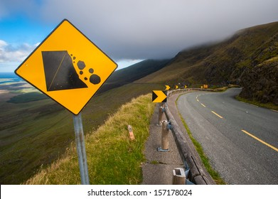 falling rocks Warning sign on a curvy road