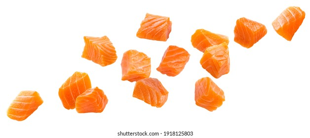 Falling salmon slices isolated on white background with clipping path, cubes of red fish with spices