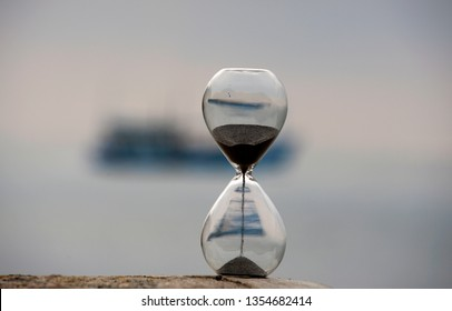 Falling sand in an hourglass with blur ship and sea in background