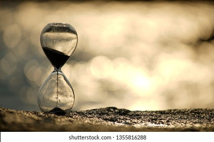 Falling sand in an hourglass with gold bubble blur sunset sea in background