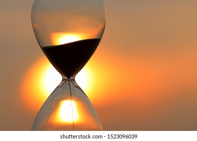 Falling sand in a hourglass at sunset sky background.