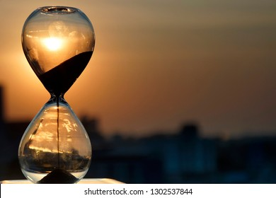 Falling sand in a hourglass with twilight sky background