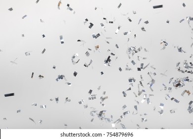 Falling silver confetti pieces on gray
