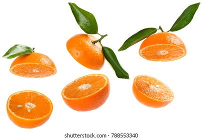 Falling sliced tangerines with green leaves isolated on white background.