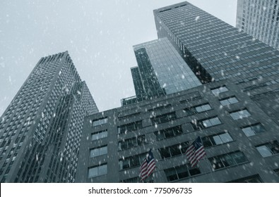 Falling snow in New York City skyline with urban skyscrapers in Manhattan, USA