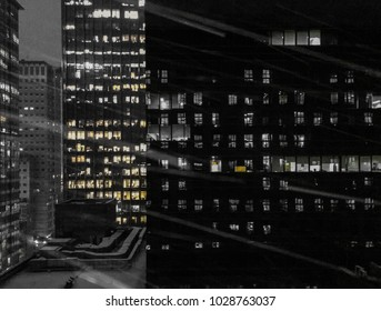 Falling Snow at night in front of window on the background of high rise buildings in the City.