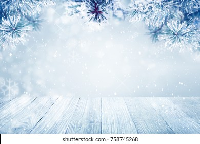 Falling snow on pine tree branches and wooden deck background, copy space