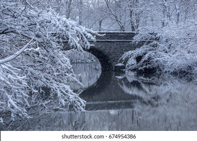 Falling snow over snow covered trees framing a stone bridge reflected in the mirror - like river water during winter In the park, Sharon Woods, Southwestern Ohio, USA