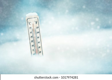 Falling snow in winter and a thermometer.